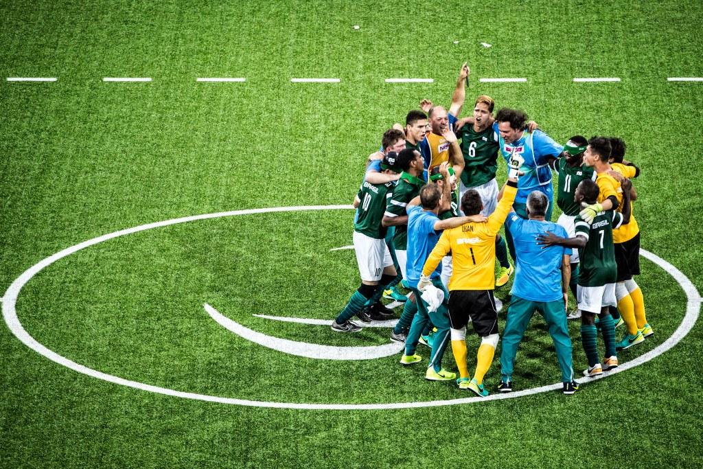 Foto tira de cima. Seleção brasileira de futebol de cinco reunida em no meio do campo verde. Na imagem, aparece 14 homens abraçados comemorando a vitória. Suas expressões são de felicidade e alegria, alguns gritam enquanto pulam com os braços levantados. A farda dos goleiros é blusa de mangas compridas amarela, short preto, meião amarelo e chuteira verde. Os demais jogadores vestem uma blusa que na frente é verde e atrás azul e short branco. Os técnicos usam blusa e calça azul claro.